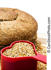 Golden flax seeds with bread and heart closeup isolated