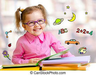 Happy child girl in glasses reading books in library