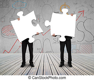 Two people holding puzzles to connect business doodles...