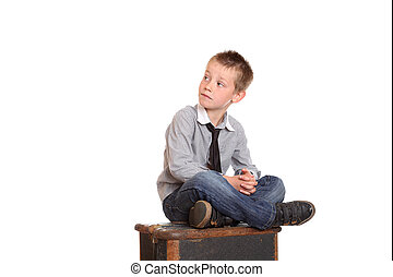 Young boy sat cross-legged on old trunk looking over his...