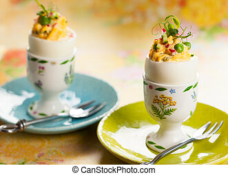 Stuffed eggs in egg cups - Stuffed eggs filled with...