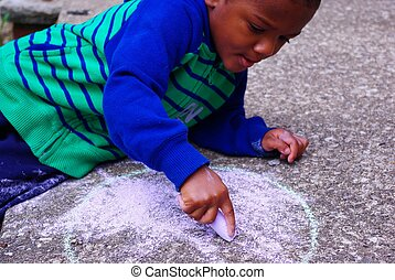 Chalk Drawing - Image of an African American boy drawing...