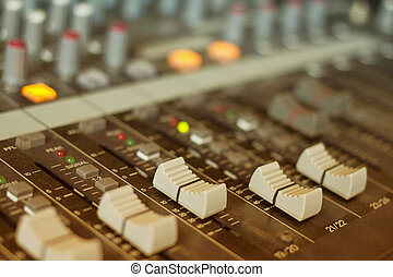 audio mixing console with faders and adjusting