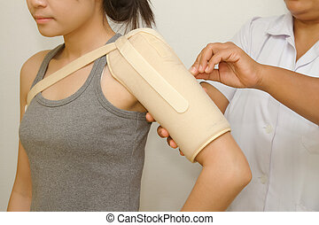 Physiotherapist checking woman's shoulder for release pain -...