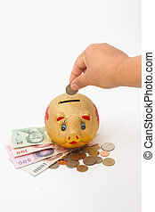 Saving, Female hand putting a coin into piggy bank for retirement plan