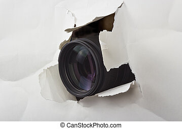 hole in a sheet of paper - photo lens protruding through a...