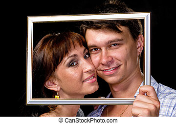 Happy couple in frame. Beautiful young couple looking through a picture frame and smiling  on black