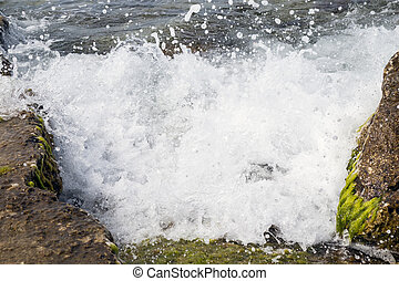 A marine wave breaks against off-shore stone