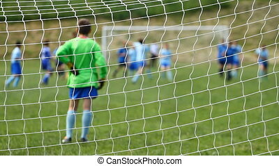 Children soccer from behind net - Children soccer game from...