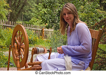 Woman Spinning Yarn in Garden - This Caucasian woman is...