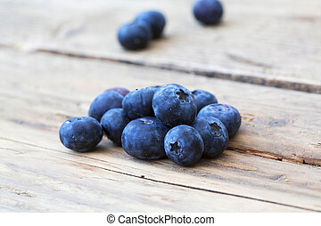 macro shot of blueberies on wooden background - fresh local...