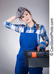 Tired woman with a toolbox