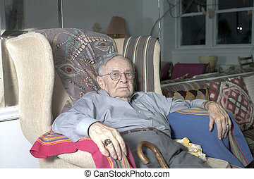 Senior man sitting on couch - A senior man sits on his couch...