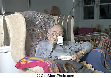 Senior man sitting on couch with cup drinking