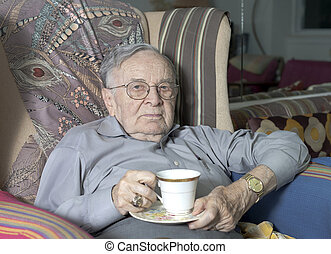 Senior man sitting on couch with drinking cup - A senior man...