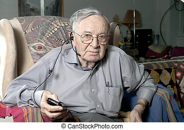 Senior man sitting on couch with headphone - A senior man...