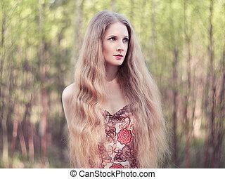 Beautiful young woman in summer garden