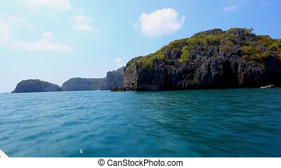 Sailing of speed boat next to a rock islands in accelerated...