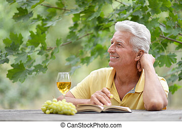 Old man sitting at a table drinking wine and reading a book