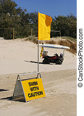 Swimming caution sign and flag on beach.