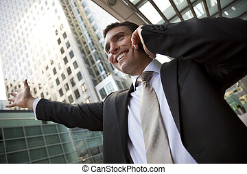 Businessman On His Cell In The City - A young male executive...