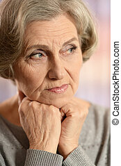 Portrait of elderly woman isolated on colored background
