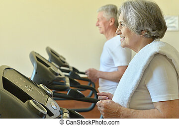 Couple exercising in gym - Portrait of a senior couple...