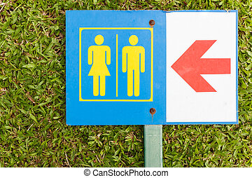 Guide post arrow to restroom for men and women on grass -...