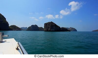 Sailing speedboat between islands in the ocean with views of...