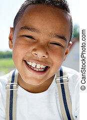 Young boy smiling with suspenders