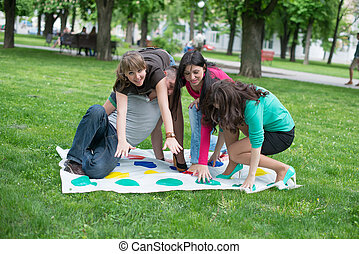 students play the game twister - Students play a game in the...
