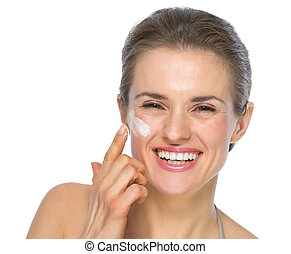 Happy young woman applying creme on face