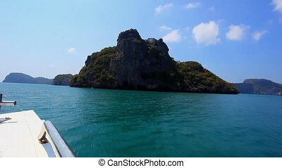 Sailing speedboat next to islands in the ocean with views of...