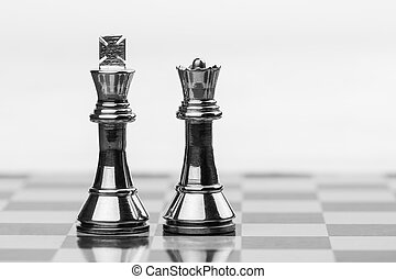 King and Queen - Rugged brass chess king and queen pieces on...