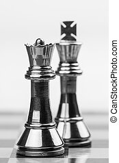 Powerful Queen - Rugged brass chess queen and king pieces on...