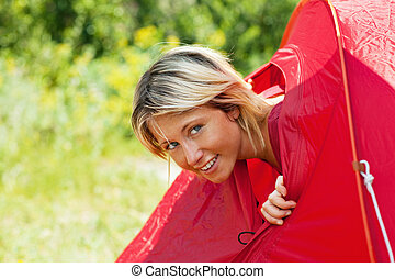 woman in tent - young blonde woman going out from tent and...