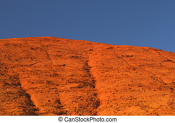 Ocher hill and blue sky. - Red and orange ocher hill with...