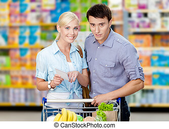 Pretty couple discussing the shopping list and chosen products