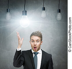 Amazed man with open mouth and light bulbs overhead -...