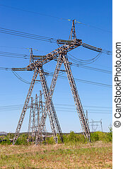 Standard overhead power line transmission tower against blue...
