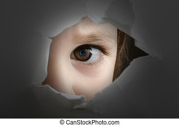 frightened child is spying through a hole in wall