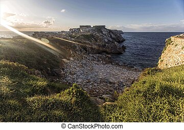 Flaring Beach - A rocky beach with greenery and a flaring...