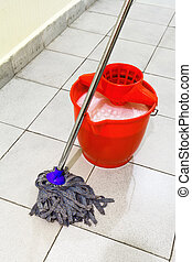red bucket with washing water and mop the floor - red bucket...