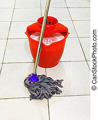 red bucket with foamy water and mop the floor - red bucket...