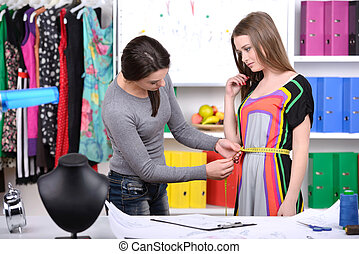 Tailors - Fashion designers at work. Two cheerful young...