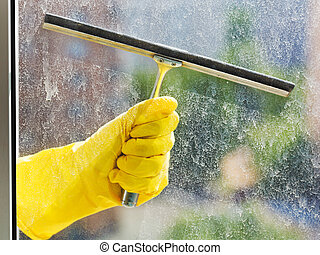 hand in yellow glove washes window by squeegee - hand in...