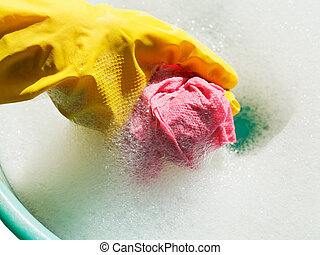 hand in yellow rubber glove rinsing rag in soap suds water