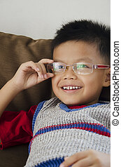 Kids glasses  - Smiling boy wearing a red hand pin.