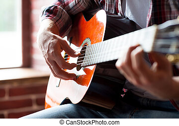 Virtuoso play. Close-up of man playing acoustic guitar while...