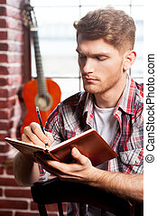 Creative composer. Handsome young man writing something in...